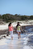 Two women walking barefoot along the seashore Stock Photography
