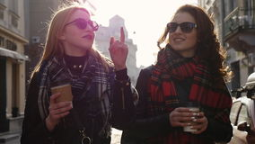 Two women walking in the city, steadicam shot. Happy, young pretty girlfriends talking in the city stock video footage