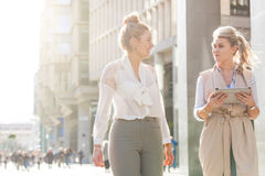 Two women walking in the city and talking Royalty Free Stock Images