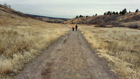Two Women Walking Down a Dirt Road. This picture of a dirt trail, with two women in the distance walking down the trail, was taken in the Rocky Mountains Royalty Free Stock Image