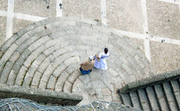 Two women walking down the stairs in the street of Porto, Portugal. View from above. A senior lady and a young woman in a dress walking down an old stone stairs Stock Image