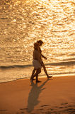 Two women walking on a golden beach Royalty Free Stock Image