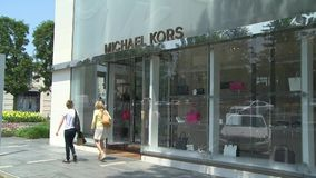 Two women walking by Michael Kors stock footage