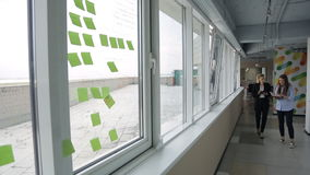 Two women are walking in office corridor. There are papers of green neon color with notes stuck on big windows with view of roof stone or brick fencing of grey stock video footage
