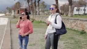 Two women walking outside. Two women walking, woman talking use smartphone, a woman drinks a drink from a bottle stock video