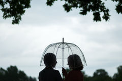 Two women walking park in rain and talk. Friendship and people communication. Rainy Royalty Free Stock Photo