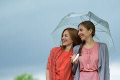 Two women walking park in rain and talk. Friendship and people communication. Stock Photo