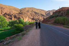 Two women walking on a road in Morocco royalty free stock photography