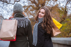 Two women walking with shopping bags outdoors Royalty Free Stock Image