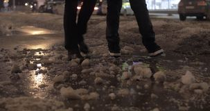 Two people walking in the winter city at night. Two women walking on the sidewalk in evening winter city. They passing over pieces of ice on their way. Only feet stock footage