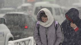 Two women walking through snow on city sidewalk during snowfall, blowing snow