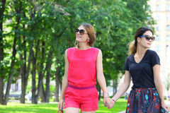 Two women walking in the summer city Stock Photos