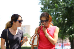 Two women walking in the summer city Stock Images