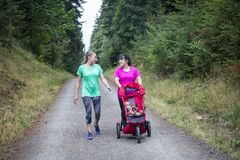 Two women walking and talking together on a trail with a baby stroller royalty free stock photography