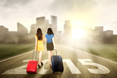 Two women walking to the future. Rear view of two women carrying suitcase walking on the road towards the future 2015 Royalty Free Stock Photography