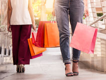 Two women walking to shopping, sale, consumerism and people concept. Royalty Free Stock Image
