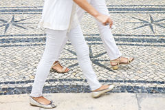 Two women walking in a typical Portuguese street paved in little stone Portugal Stock Images
