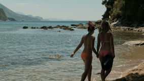 Two women walking on water by coastline in open air. Holding hands they slowly goes along warm aqua near sandy beach enjoying summer weather and noise of surf stock footage