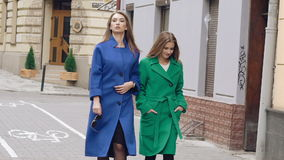 Two women walks runway in cashmere coats on the street. Slowly stock video