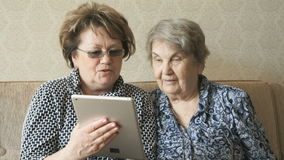 Two women watch photos using a electronic tablet. Two women sit on the couch and watch photos using a digital tablet stock footage