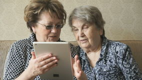 Two women watching photos on a digital tablet stock footage