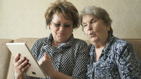 Two women watching photos on a digital tablet stock video