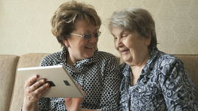 Two women watching photos on a digital tablet stock video footage