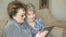 Two women watching pictures on a digital tablet stock footage