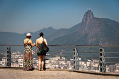 Two women watching the skyline of Rio de Janeiro from the lookout point on the Sugarloaf Mountain Stock Photo