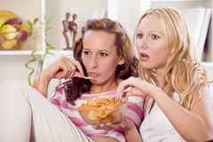 Two women watching television at home Stock Photo