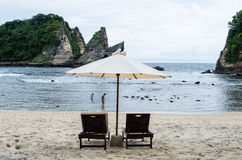 Two women in the water of Atuh Beach behind sunbeds on Nusa Penida Bali, Indonesia Stock Photo