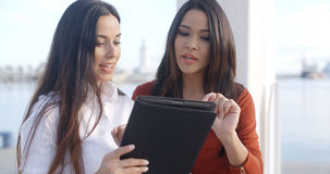 Two women on a waterfront esplanade. Two stylish attractive young women on a waterfront esplanade standing chatting and looking at a tablet computer together Royalty Free Stock Photo