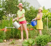 Two women watering flowers Royalty Free Stock Photos