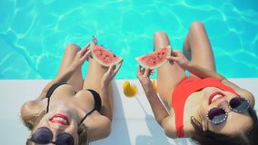Two women with watermelon slices playing with water and looking at camera, hotel. Stock footage stock video