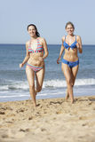 Two Women Wearing Bikinis Running Along Beach Stock Photos
