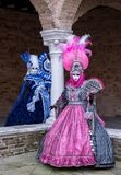 Two ladies wearing brightly colored masks and costumes at Venice Carnival. Royalty Free Stock Photos