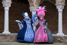Two women wearing colorful masks and costumes at Venice Carnival. Stock Images