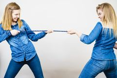 Two women having fun pulling rope. Two women wearing jeans outfit having fun pulling rope, good rivalry concept. Sporty competition Stock Images