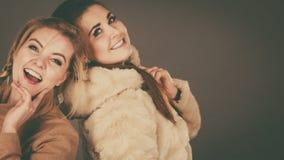Two women wearing light brown coats Stock Photos