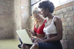 Two Women Wearing Red and White Sports Bras Sitting Near Brown Wall Bricks Royalty Free Stock Photo