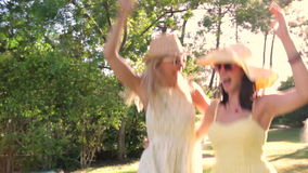 Two women wearing sunglasses and. Straw hats dance along country path.Shot on Canon 5D Mk2 at at a frame rate of 30 fps stock video footage