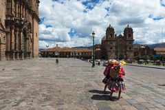 Two women wearing traditional clothes in the Plaza de Armas in the City of Cuzco, in Peru. Royalty Free Stock Image