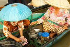 Two women weighing and selling fresh fish on a floating market. Two asian women at daytime weighing and selling fresh fish in a boat on a floating market just Royalty Free Stock Photo