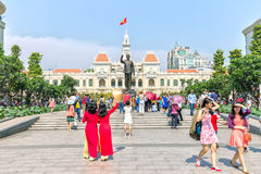Two women welcome spring before the City People's Committee. Ho Chi Minh City, Vietnam - February 10th, 2016: Two women welcome spring with red long dress Stock Photography