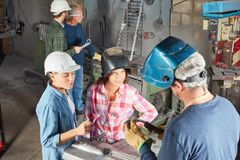 Two women in welder apprenticeship. Learning during metallurgy lesson royalty free stock photography