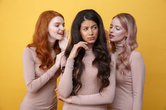 Two women whisper to their friend. Two young women whisper to their friend over yellow background stock photography