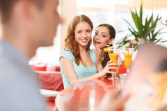 Two women whispering and smiling in cafe. Redhead girl looking at boy at next table Stock Image