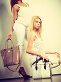 Two women in white clothes with bags handbags. Royalty Free Stock Image