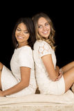 Two women white dress on black back to back smile Royalty Free Stock Photography