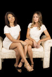 Two women white dress on black facing legs crossed Royalty Free Stock Image